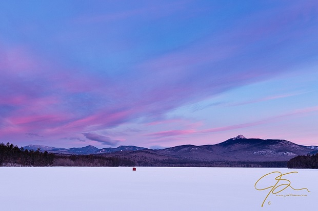 On snow covered Chocorua Lake, a lone red bob house, or ice fishing shack, sits under the pastel pink and purple early mornig sky. Off in the distance, image right, Mt. Chocorua stands tall with its snow covered summit catching the first hints of pink alpenglow as the sun crests the horizon.
